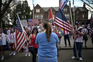A registered nurse stands in front of protestors rallying outside of the Minnesota governor's mansion to demand an end to the coronavirus lockdown.
