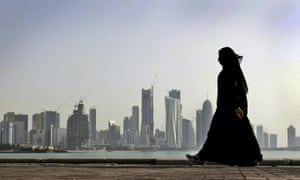 A Qatari woman walks in front of the city skyline in Doha.