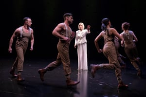 A woman in a white pantsuit with men and women in militaristic overalls running around her in a circle