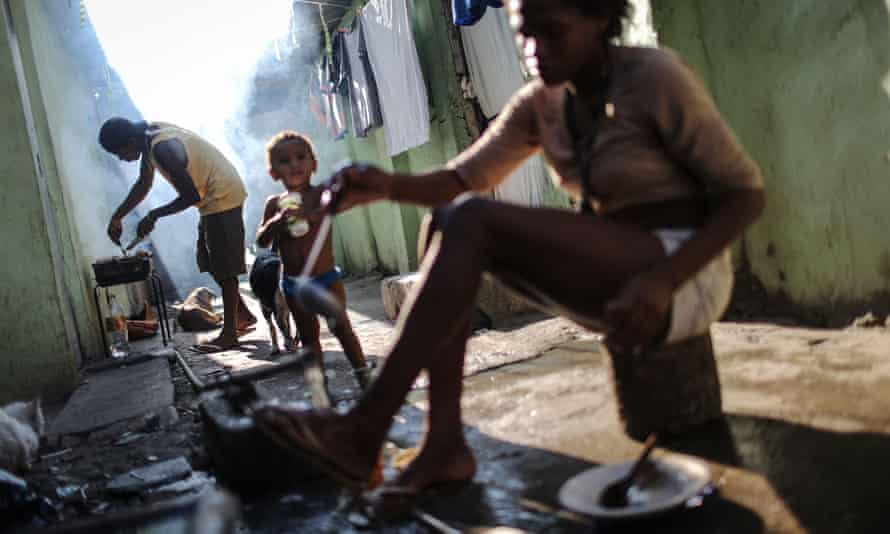 A man cooks a meal in Maré favela. 'We still don't have what is most important: peace.'