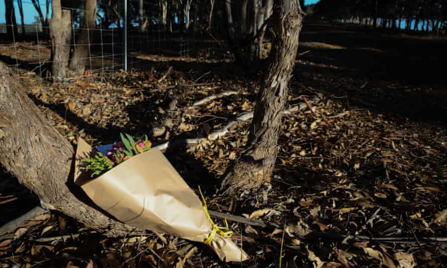 Flowers are left next to a police roadblock where police are investigating the death of seven people in suspected murder-suicide in Osmington, east of Margaret River, 11 May 2018.