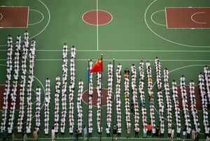 Children line up for a flag-raising ceremony as they return to school in Shanghai, China
