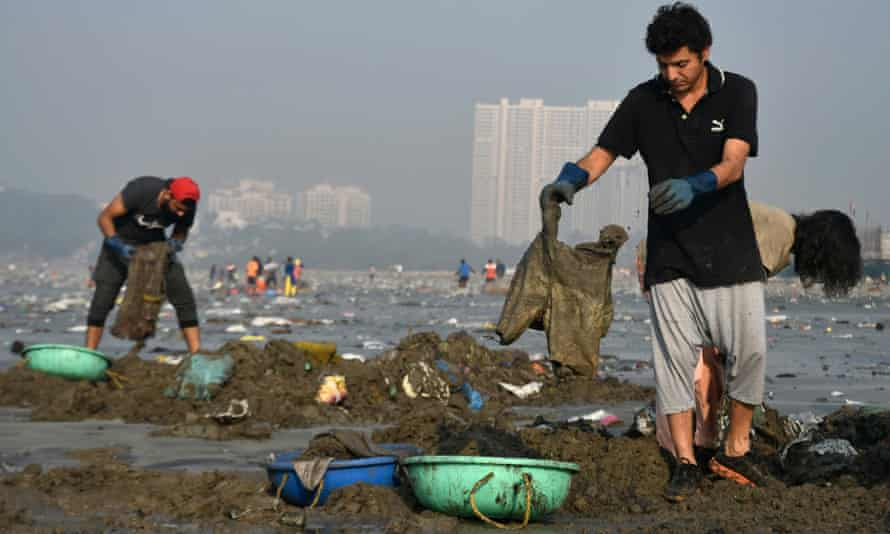 Workers and volunteers help clean up Versova beach in Mumbai, India