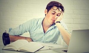 A sleepy young man sits at his laptop