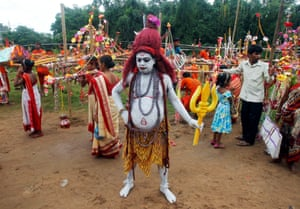 A kanwariya, a Hindu devotee dressed as Lord Shiva, joins a religious procession in Tripura state during the holy month of Shravan
