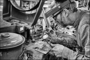 Jewellery designer Jon Dibben works in his Surrey studio, heating a piece of gold until molten with a burner