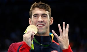 Michael Phelps holds up four fingers alongside his gold medal signifying his historic achievement.