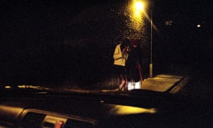 A view from a car of a man and a young girl on a street at night (posed by models)