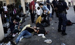 People try to recover after clashes with the police during a protest at the Lesvos Port