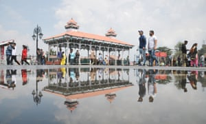 Pedestrians in Shimla reflected in a puddle. Most rainwater in the city washes away before it can be collected.