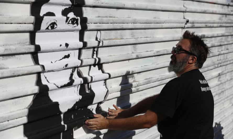 Manuel Oliver, who lives in Florida and is the father of slain high school student Joaquin Oliver, works on a painting on the US border wall in Tijuana, Mexico, that will carry the Spanish message: 'On the other side they also kill our children.'