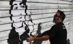 Manuel Oliver, the father of slain high school student Joaquin Oliver, works on a painting on the US border wall, part of his activism since the death of his son.