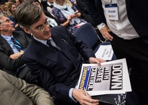 Jacob Rees-Mogg signs a poster that reads 'Down with state control' at the Tory conference.