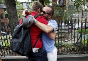 Drew Ginsburg, left, and Chris Heinbaugh from Texas embrace as they stand outside the Stonewall Inn in the Greenwich Village neighborhood of New York