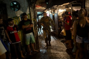 A police officer patrols past residents during a police operation at the favela of Rocinha in Rio de Janeiro, Brazil.