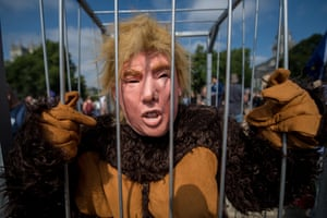 A protester dressed in a Trump mask and gorilla costume stands in a cage, London