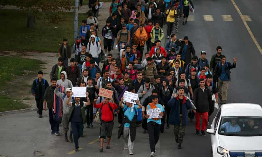 People hold up signs as they approach the Hungarian border in Serbia.