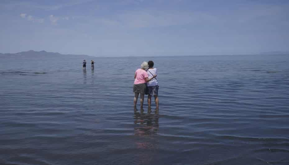 Visitors stand in the shallow waters of the Great Salt Lake.