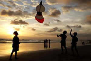 Bali, Indonesia Boys fly their kite during sunset on Kuta beach, as the island reopened after a three-month virus lockdown.