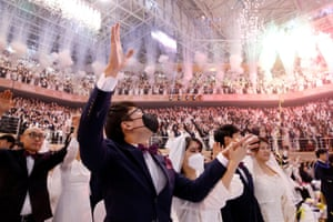 Brides and grooms celebrating in audience