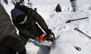 Rescuers used chainsaws to cut through the hard snow.