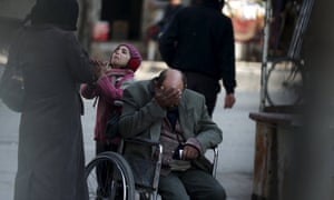 A girl with her father on a wheel chair, ask for help to pay a medical bill from passers by, in Douma, Syria.