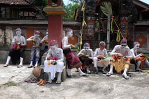 Ngerebeg festivalgoers in Bali, Indonesia, take a break before swarming into a temple to 'neutralise the negative effect of humans on the environment
