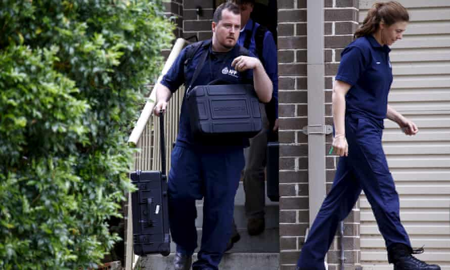 Federal police carry equipment as they leave a house during early morning raids in western Sydney on Wednesday.
