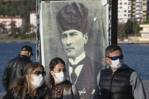 Turks wearing masks as they walk past a poster of the republic's founder, Mustafa Kemal Ataturk, in Canakkale.