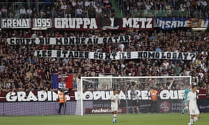 Metz supporters hold banners during the Ligue 1 game against PSG; the referee stopped the match until the banners were removed.