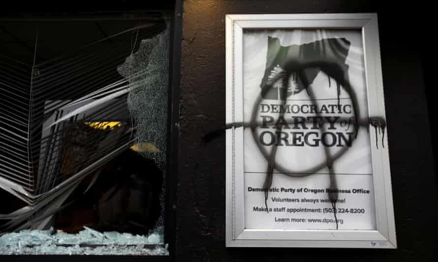 A smashed window and anarchist symbol spray-painted on the building in Portland, Oregon, on 20 January.