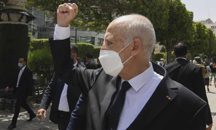 Tunisia's president, Kais Saied, raises his fist to bystanders in Tunis.