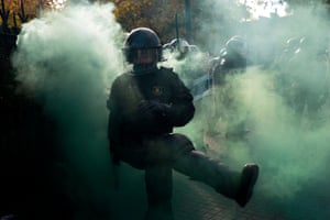 A member of the Catalan regional police force kicks away a smoke bomb.