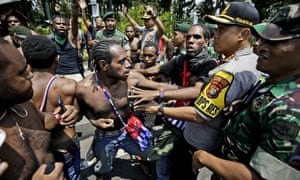 Papuan activists scuffle with police and soldiers during a rally near the presidential palace in Jakarta. President Widodo has pledged action against racial and ethnic discrimination against Papuans