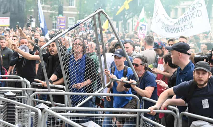 People throw fencing during an anti-vaccine and anti-lockdown demonstration outside Downing Street.