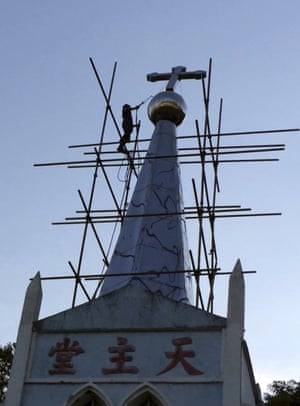 A cross atop the Lower Dafei Catholic church is removed by a Chinese government worker with a cutting torch.