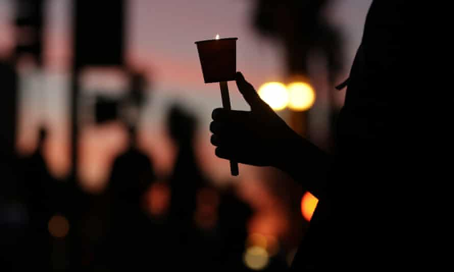 A woman holds a candle during a vigil to honor shooting victims in San Bernardino, California