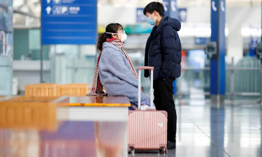 People wear face masks while waiting on the platform of the Airport Express train at Beijing Capital Airport