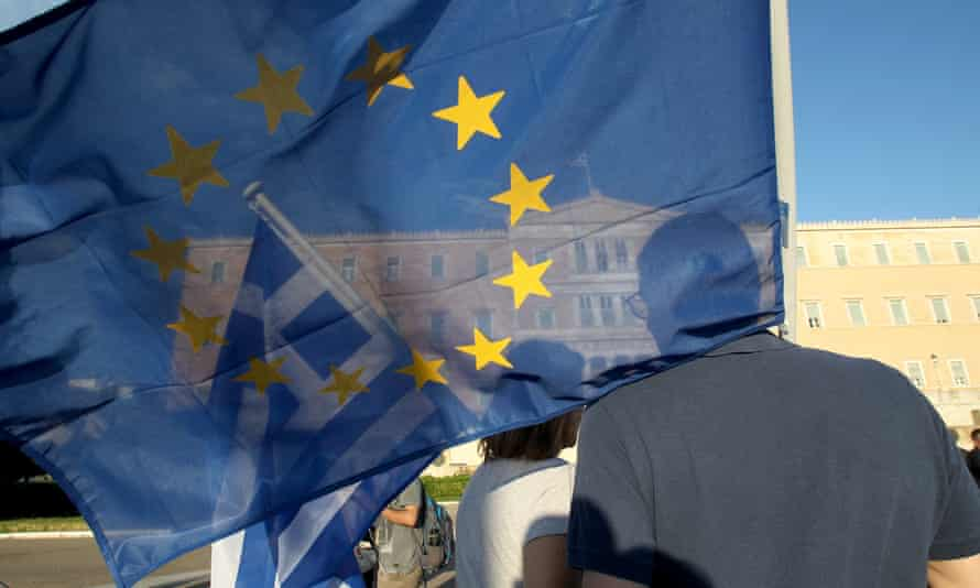 Demonstrators rally in front of the Greek parliament with Greek and EU flags