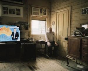 A elderly man sitting inside his home