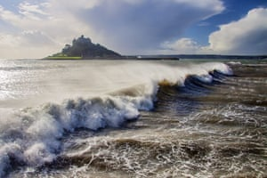 View towards St Michael's Mount in Cornwall with crashing waves and ocean spray pounding the shore.