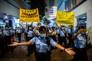 Police move people on as they gathered in the Causeway Bay district of Hong Kong on June 4, 2021, after police closed the venue where Hong Kong people traditionally gather annually to mourn the victims of China's Tiananmen Square crackdown in 1989 which the authorities have banned citing the coronavirus pandemic and vowed to stamp out any protests on the anniversary.
