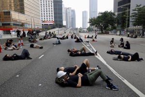 Protesters who camped out overnight take a rest along a main road near the Legislative Council, as part of the ongoing demonstrations against the extradition bill.