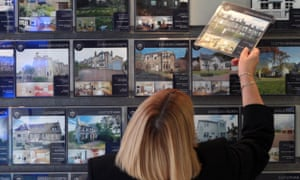 A woman looking at houses for sale at an estate agent