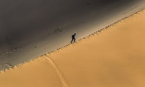 Gansu, China: A man climbs a sand dune near Dunhuang, a stop on the ancient Silk Road, established at an oasis that contains Crescent Lake