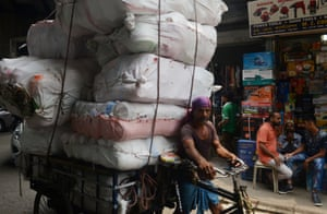 An Indian labourer uses a rickshaw to transport material through the wholesale market area of Kolkata