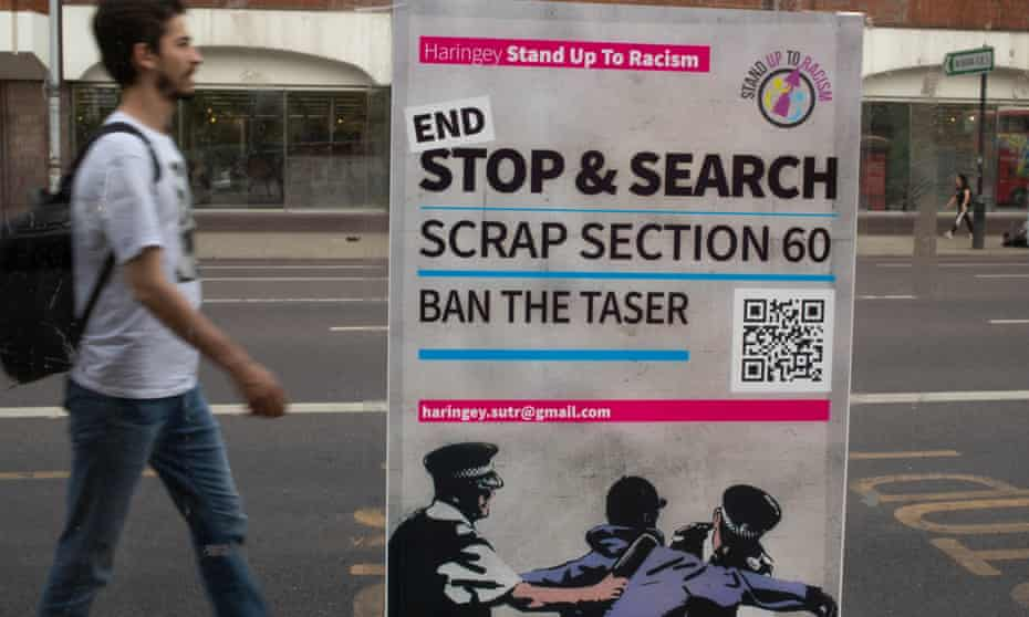 A man walks past a poster calling for an end to suspicion-less stop and search in Tottenham.