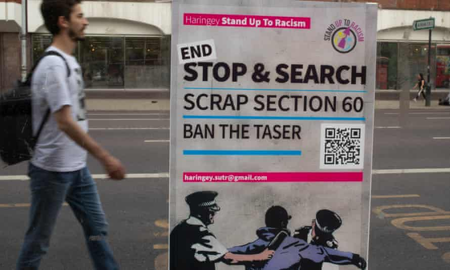 A man walks past a poster calling for an end to section 60 near Tottenham police station.