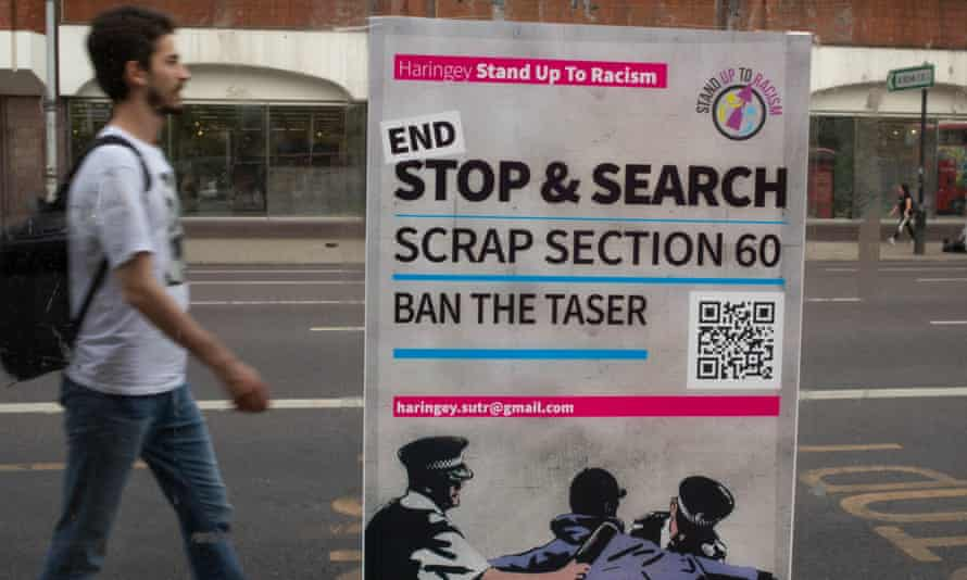A man walks past a poster near Tottenham police station in London calling for an end to section 60, which allows police to stop and search a person without reasonable suspicion.