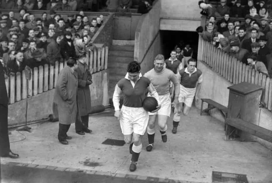 Gordon Smith leads out the Hibs players against Manchester United in a friendly in 1952.